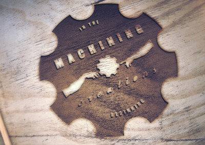 Engraved wood logo of local machine shop business.